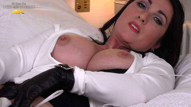 Miss Hybrid magic wand and tits out on the bed.