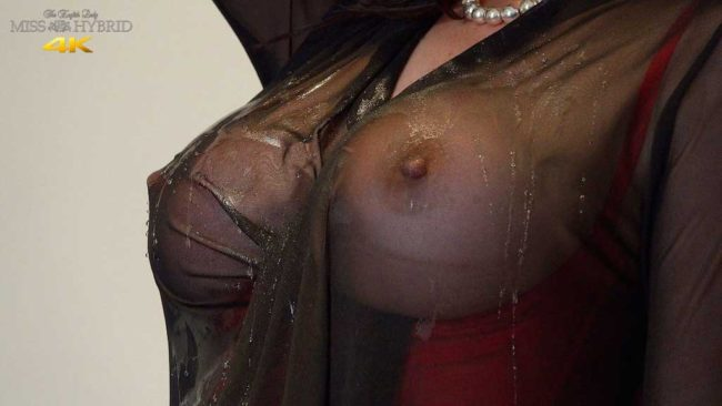 Leather thigh boots and sexy red stockings Miss Hybrid pours water over her magnificent tits.