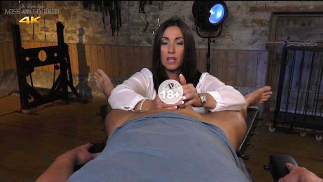 Dungeon mistress Miss Hybrid teases her victims caged cock.